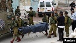 Израиль әскерилері өздеріне шабуылдау кезінде атып өлтірді делінген палестиналықтың денесін әкетіп барады. Хеврон, наурыз 2016 жыл (Көрнекі сурет).