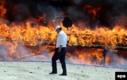 An Iranian policeman walks past a cloud of smoke rising from a pile of drugs that was set on fire during an incineration ceremony for some 50 tons of illicit narcotics seized by the authorities. (file photo)