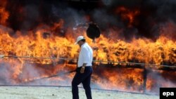 Iran -- An Iranian policeman walks past a cloud of smoke rising from a pile of drugs set on fire during an incineration ceremony of some 50 tons of illicit drugs in an annual ritual in Tehran, June 26, 2014