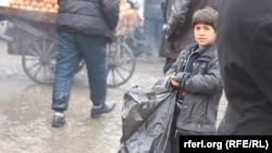 آرشیف، یک کودک در حال فروش خریطه پلاستیکی در شهر کابل