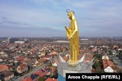 A golden statue of Mary stands atop a church spire in southern Budapest.