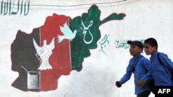 Afghanistan -- Schoolboys walk past a mural of painted with the colours of the Afghan national flag in Kabul, 21May2012