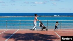 Жінка з дитиною гуляє на набережній пляжу Лас-Кантерас на острові Гран-Канарія, Іспанія, 26 квітня 2020 року