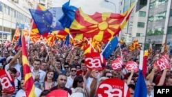 "People wave Macedonian and European flags as they attend a campaign rally in Skopje on September 16 for a ""yes"" vote ahead of a referendum scheduled for later this month."