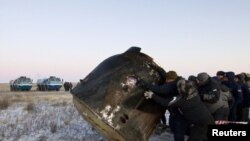 Ground personnel roll the Soyuz TMA-02 capsule after it landed while carrying ISS crew members near the town of Arkalyk, Kazakhstan.