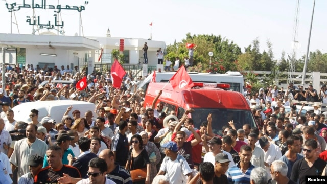 Protesters escort the body of assassinated Tunisian opposition politician Muhammad Brahmi in Tunis on July 25.