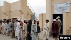 Internally displaced refugees queue for aid at the entrance of a food distribution center in Bannu. (file photo)