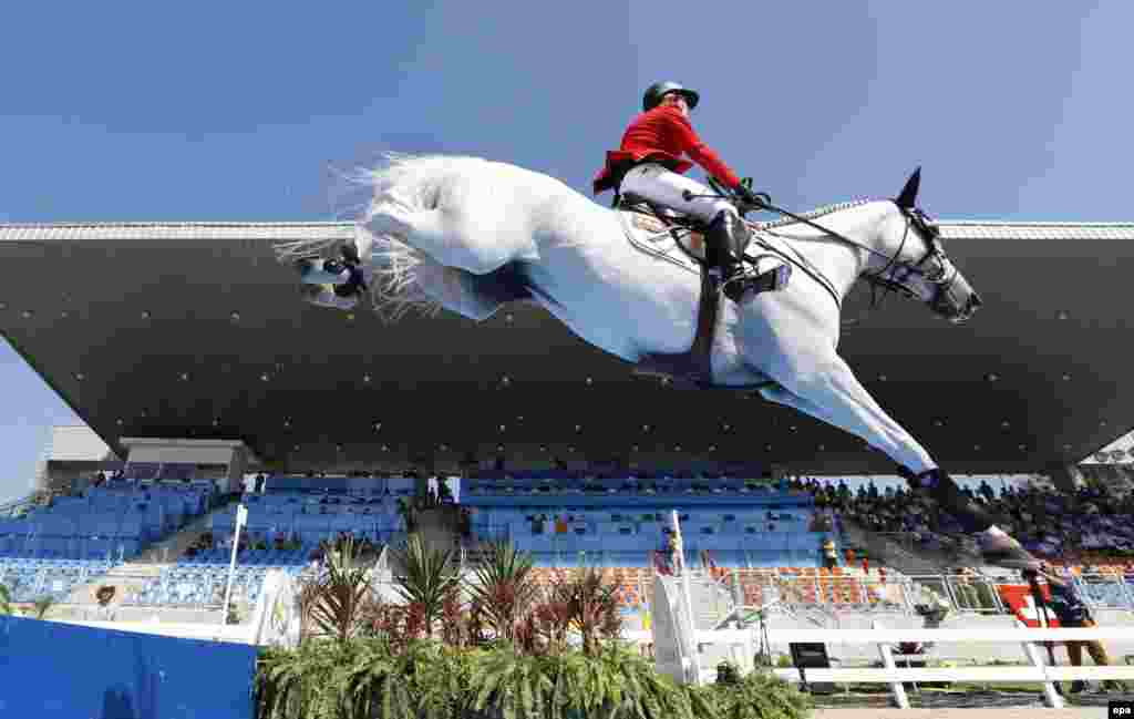 Meredith Michaels-Beerbaum of Germany rides her horse, Fibonacci, during the individual jumping qualifier.