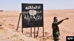 Një pjesëtar i qeverisë siriane bën selfie para një tabele të grupit ekstremist Shteti Islamik afër qytetit Raka