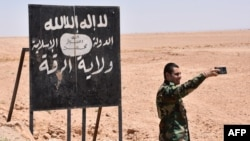 Человек в камуфляжной форме фотографируется на фоне билборда экстремистской группировки ИГ. 9 июля 2017 года.