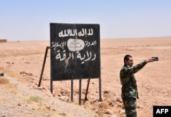 A Syrian soldier takes a selfie with an Islamic State (IS) group billboard at the Ithraya-Rasafa highway near the city of Raqqa on July 9, 2017.
