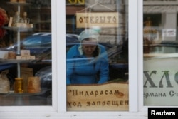 "An employee arranges products on display next to a sign saying ""No pederasts allowed"" at a Bread And Salt store in central Moscow."
