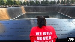 U.S. -- A woman reflects at the 9/11 Memorial during ceremonies marking the 12th anniversary of the 9/11 attacks on the World Trade Center in New York. September 11, 2013.