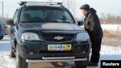 Житель Актобе рассматривает автомобиль, пригнанный из России на продажу в Казахстане. 19 декабря 2014 года.