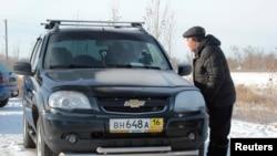 Местный житель у автомобиля с российскими номерами. Актобе, 19 декабря 2014 года.