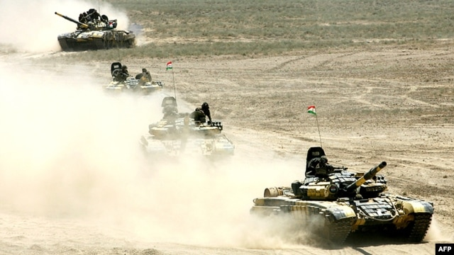 Russian-built tanks roll under Tajik flags during Peace Mission 2012 joint counterterrorism military exercises of the troops from the six countries in the Shanghai Cooperation Organization in Khujand in June 2012.