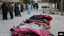 The bodies of the police cadets (covered by blankets) and the body of a suspected militant lay on the ground outside a hospital after an attack by suspected militants at a police training center in Quetta on October 25.