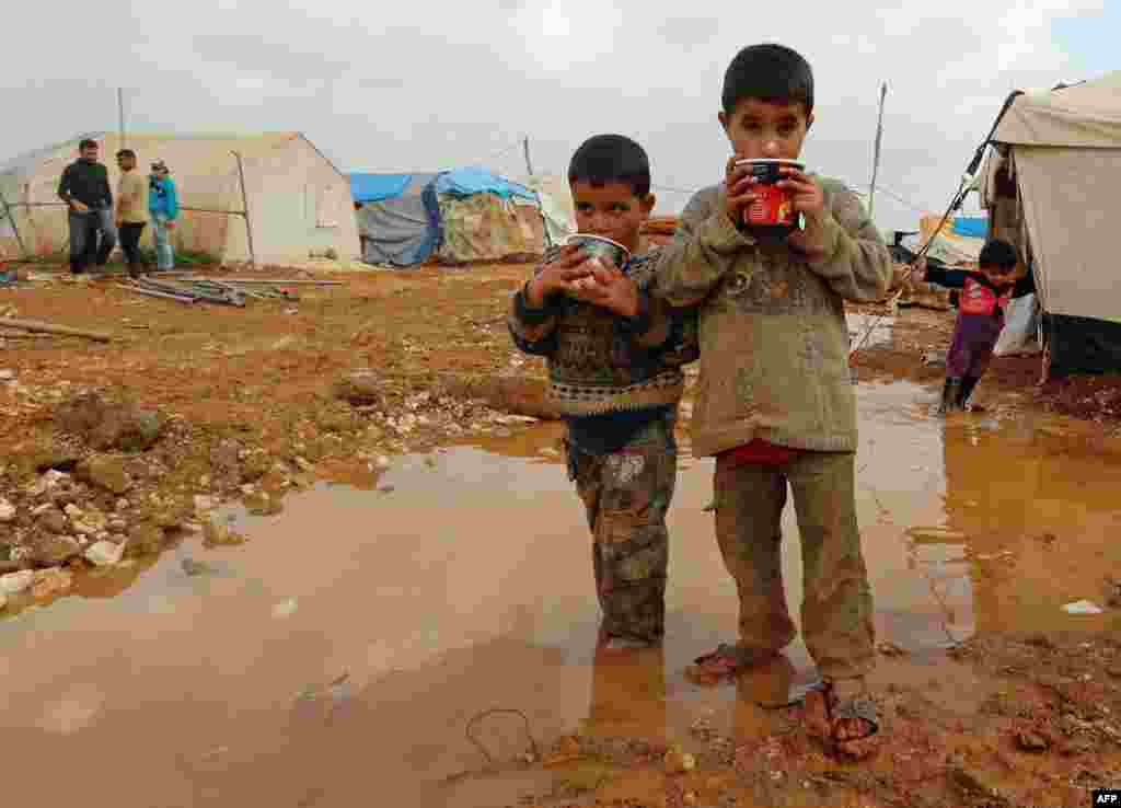 Displaced Syrian children stand in muddy water after heavy rains in the Bab Al-Salama camp for people fleeing the violence in Syria, on the border with Turkey. (AFP/Baraa al-Halabi)