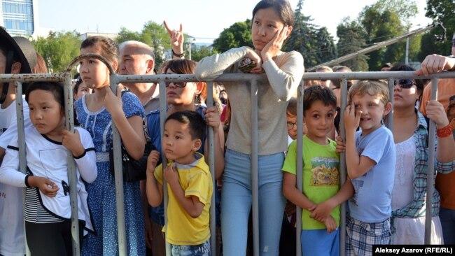 Молодежь, дети и взрослые стоят за ограждением у сцены во время мероприятия в Алматы.