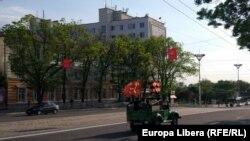 Camionetă militară pe o stradă din Tiraspol cu drapelul URSS și așa-numita panglică a Sfântului Gheorghe, promovată în ultimii ani de Rusia drept simbol al Zilei Victoriei
