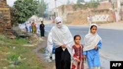 Девочки возвращаются вместе с матерью домой после уроков в школе. Долина Сват, 9 октября 2013 года.