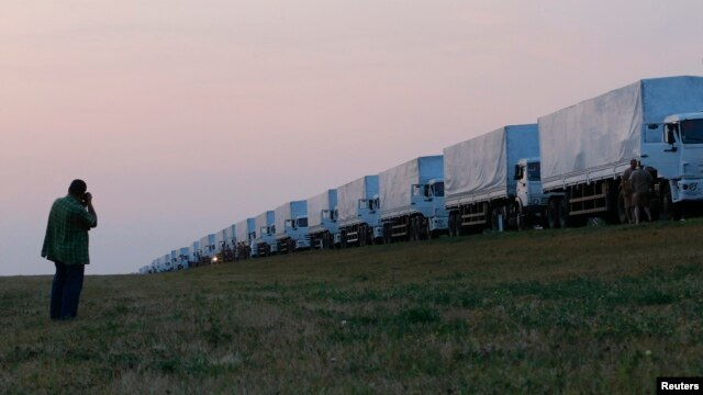 A man takes a picture of a Russian convoy of trucks carrying what Moscow says is humanitarian aid for Ukraine after the convoy stopped along a road near the Russian city of Yelets on August 12.