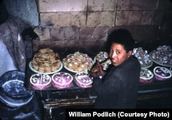 A boy decorates cakes, cookies, and other sweets.