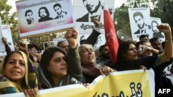 Pakistani rights activists hold images of bloggers who have disappeared, during a protest in the eastern city of Lahore on January 12.