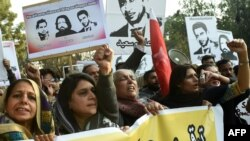 Pakistani rights activists hold up pictures of bloggers who have disappeared during a protest in Lahore in January 2017.