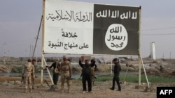 Iraqi government forces gather under a billboard bearing slogans of the Islamic State (IS) group and its trademark flag, in the town of Heet, in Anbar province, April 2016.