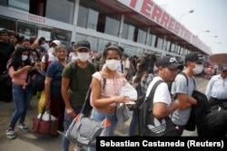 Когда правительство Перу ввело карантин и комендантский час, около миллиона мигрантов покинули столицу на автобусах, чтобы добраться домой в провинцию. Очередь на автовокзале в Лиме, 16 марта 2020 года