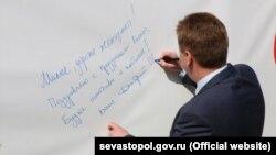 Дмитро Овсянников підписує вітальну листівку. Севастополь, 8 березня 2017 року