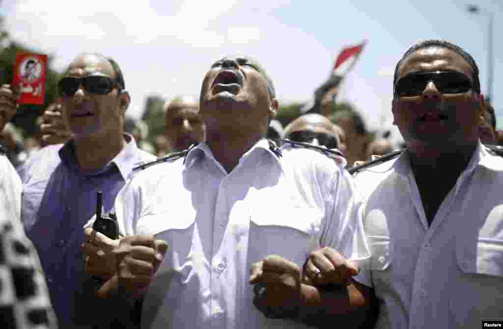 A police officer shouts 'Leave' during an anti-Morsi protest with other police officers and protesters after attending the funeral of Brigadier General Mohamed Hani, a senior police officer from Alexandria, in Alexandria.