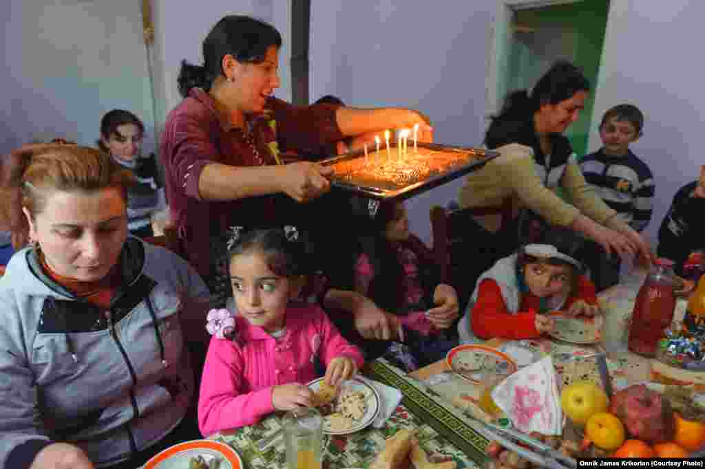 Ethnic Armenian and Azeri children attend a friend's sixth birthday party, where everyone shares a table with regional dishes.