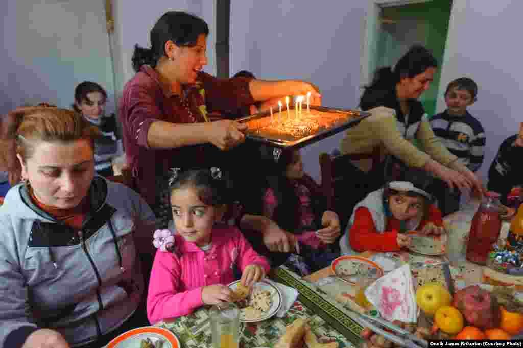 Армянские и азербайджанские дети отмечают день рождения 6-летней азербайджанской девочки за столом, уставленным местными блюдами.