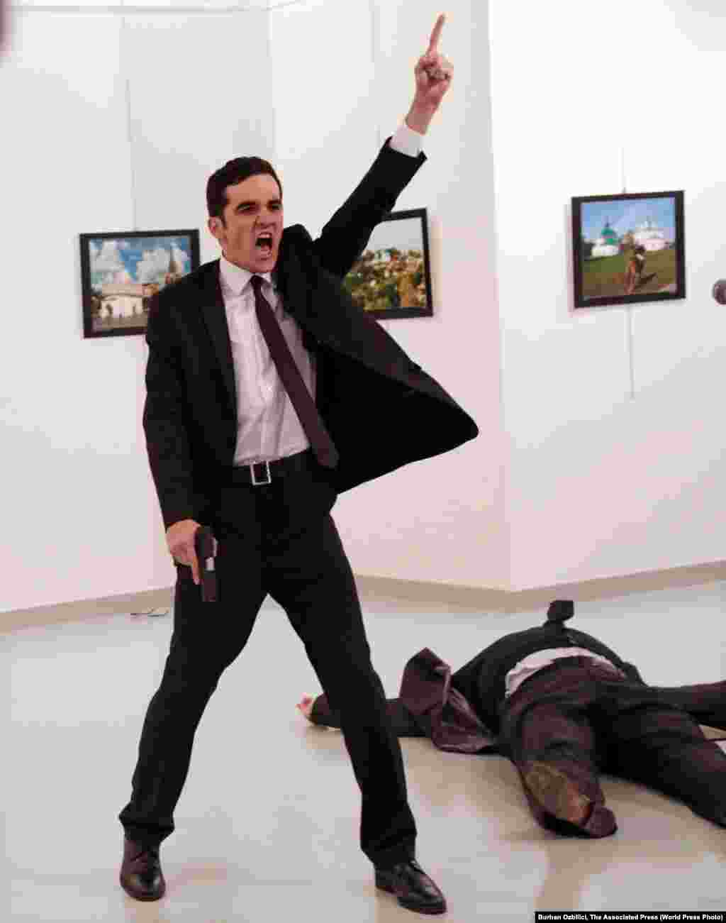 "Mevlut Mert Altintas shouts after shooting Andrei Karlov, the Russian ambassador to Turkey, at an art gallery in Ankara, Turkey, December 19, 2016. The winning World Press Photo Of The Year, from Burhan Ozbilici of Associated Press, was also part of a series, ""An Assassination in Turkey"", which won the Spot News - Stories category. Ozbilici captured the moments before and after Altintas, an off-duty policeman, drew a handgun and shot Karlov at a photo exhibition."