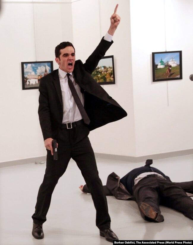 Mevlut Mert Altintas duke bërtitur pasi ka qëlluar me armë zjarri ambasadorin rus në Turqi, Andrei Karlov. Fotoreporteri Ozbilici ka fotografuar Altintasin para dhe pasi ka shtënë mbi ambasadorin Karlov, i cili ishte duke mbajtur një fjalim në një galeri arti.