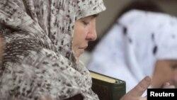 Колуна Куран китебин кармап, дуба кылып жаткан аял. Дүйшөмбү.17-сентябрь, 2010-жыл.