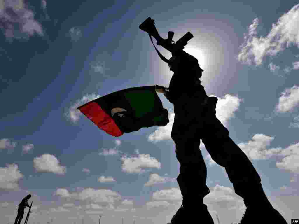 A Libyan anti-Qaddafi fighter waves the flag of the rebellion on a desert road some 30 kilometers before the eastern town of Brega on March 31, as rebels fought running street battles for the oil town, about 800 kilometers from Tripoli, with forces loyal to Libyan leader Muammar Qaddafi. Photo by AFP