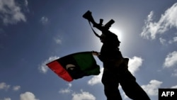 A Libyan opposition fighter waves the flag of the rebellion on a desert road some 30 kilometers from the eastern town of Brega on March 31.