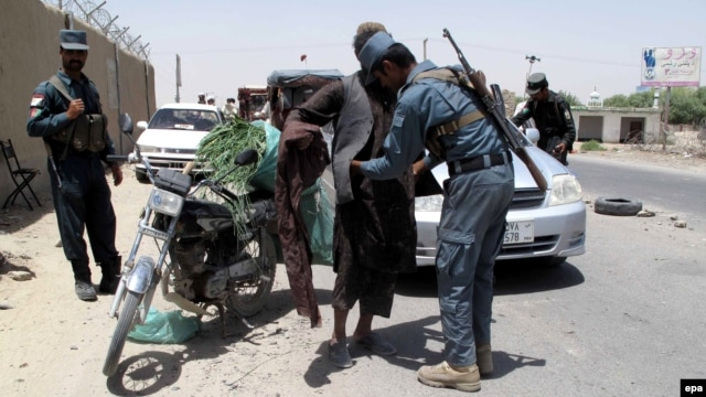 An Afghan security officer frisks a man at a checkpoint in Helmand on June 25.