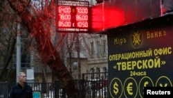 Мужчина проходит мимо пункта обмена валюты. Москва,16 декабря 2014 года.