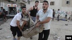 Палестиналықтар базарға әуе шабуылынан жараланған адамды әкетіп барады. Газа секторы, 30 шілде 2014 жыл.