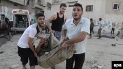 Палестинці несуть пораненого внаслідок повітряного удару по ринку в населеному пункті Шеджая, 30 липня 2014 року
