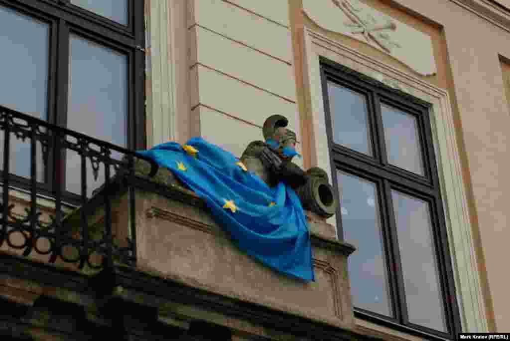 Флаги ЕС декорирует фигуры на фасаде здания в центре Львова