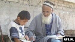 Пожилой мужчина учит мальчика основам ислама. Недалеко от центральной мечети Душанбе.