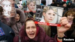 Supporters of jailed opposition leader Yulia Tymoshenko hold up her picture during a rally in Kyiv. The Tymoshenko case remains an obstacle to improved EU-Ukraine ties.