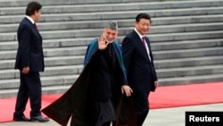 Afghan President Hamid Karzai (center) and Chinese President Xi Jinping (right) respond to children waving the national flags of their two countries at a welcoming ceremony outside the Great Hall of the People in Beijing on September 27.