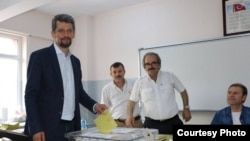 Turkey - Garo Paylan (L), an ethnic Armenian candidate of the People's Democratic Party (HDP), casts a ballot at a polling station in Istanbul, 7Jun2015.