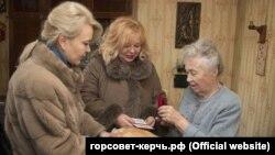 Заместитель главы горсовета Керчи Лариса Щербула (л) и глава горсовета Мая Хужина (п) вручают хлеб и юбилейную медаль керчанке